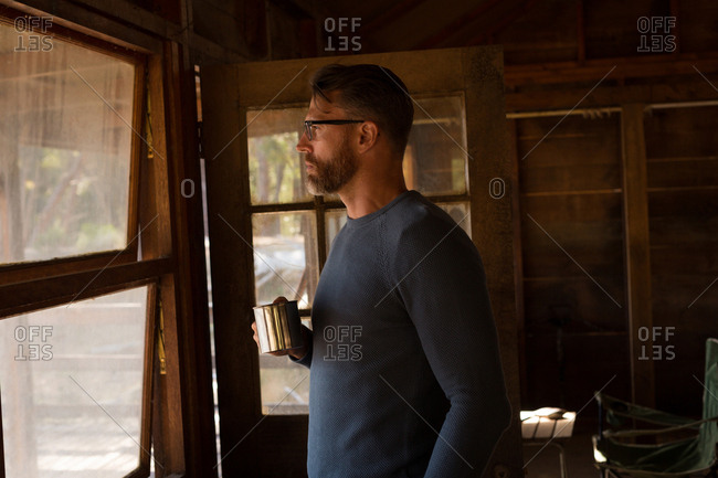 Man in log cabin with coffee mug looking through window