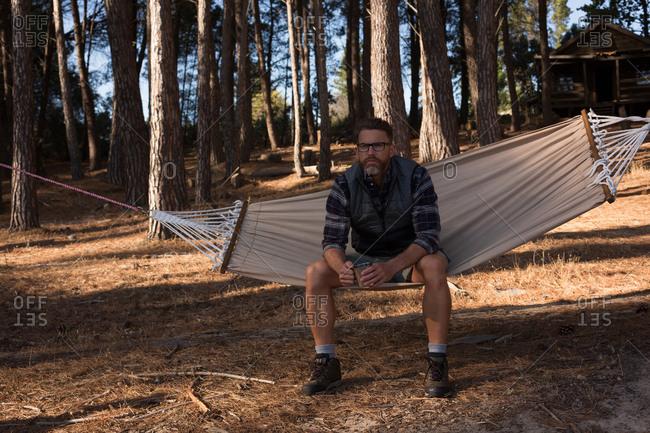 Thoughtful man with coffee mug relaxing on hammock