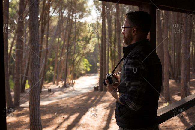 Side view of man with vintage camera standing at cabin porch