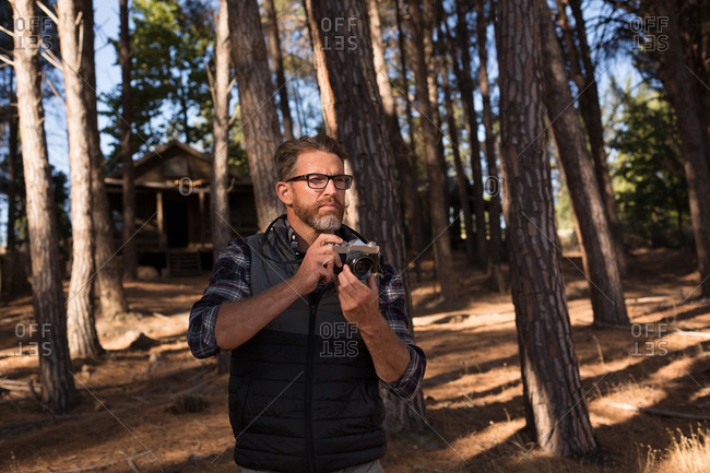 Man ready to click photo of nature with camera in forest