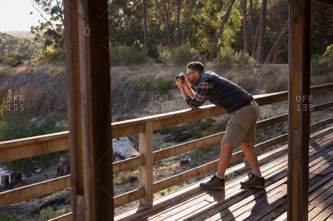 Man clicking photo with vintage camera at cabin porch