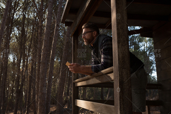 Thoughtful man with mobile phone standing at cabin porch