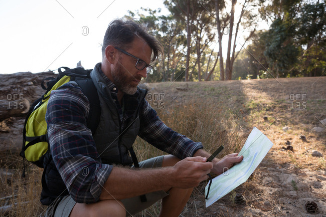 Side view of man looking at map in forest