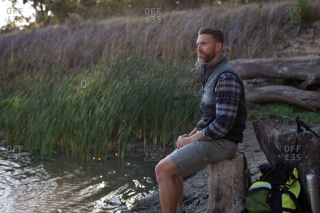 Side view of man relaxing on tree stump near river bank