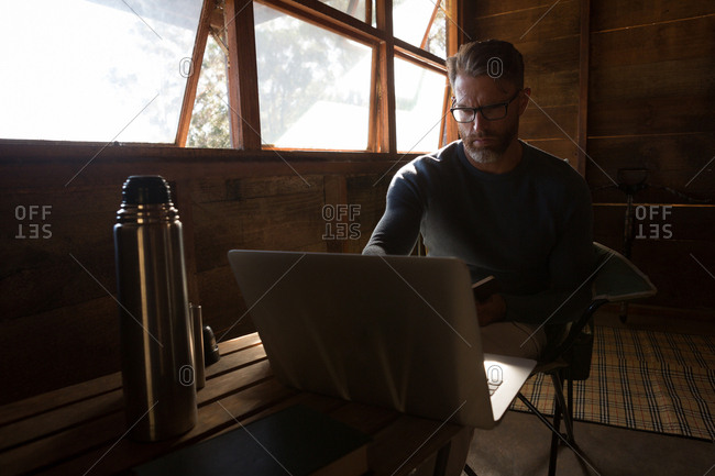 Thoughtful man using laptop at log cabin