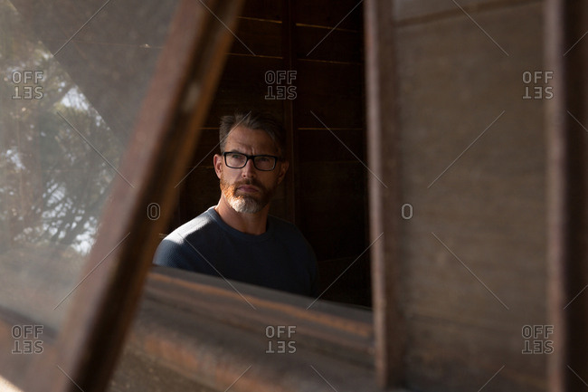 Man looking through the window in log cabin
