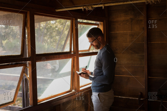 Side view of man writing note on diary at log cabin