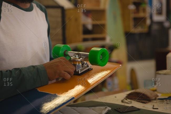 Mid section of man making skateboard in workshop