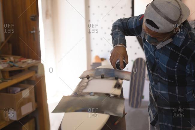 Man spray painting skateboard in workshop