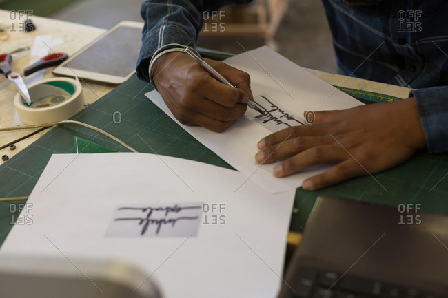 Man making design on paper in workshop