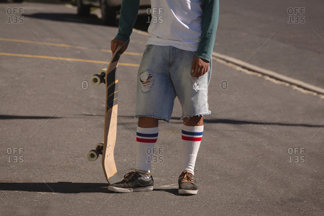 Man standing with skateboard in street on a sunny day