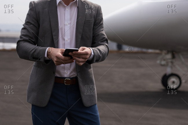 Mid section of businessman using mobile phone at terminal