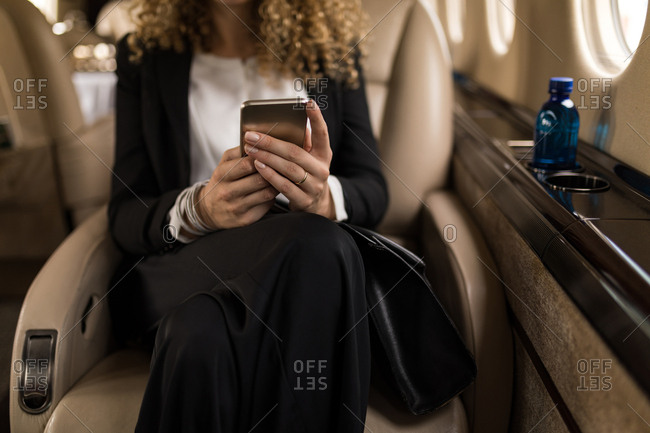 Mid section of businesswoman using mobile phone in private jet