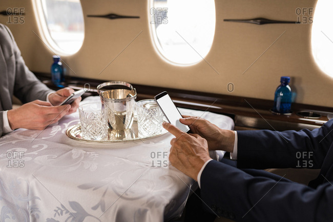 Mid section of businesspeople using mobile phone in private jet
