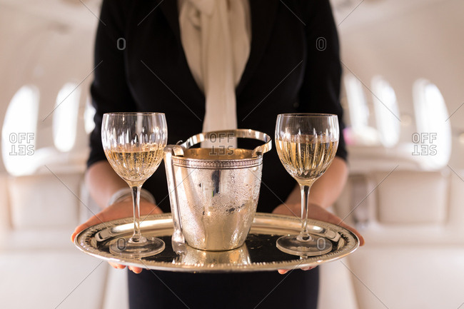 Mid section of flight attendant serving glasses of champagne in private jet