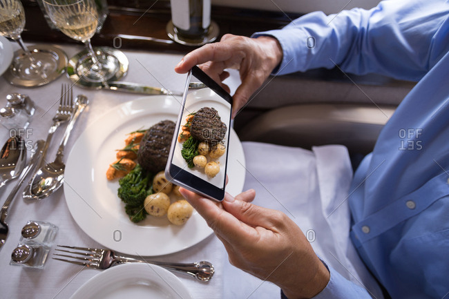 Mid section of businessman taking photo of meal with mobile phone in private jet