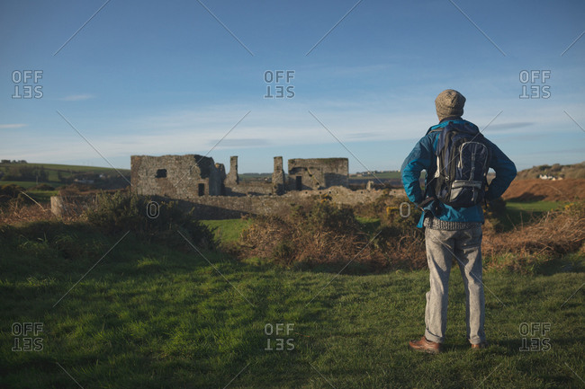 Rear view of male hiker standing with backpack at countryside