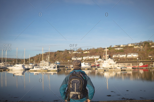 Rear view of male hiker standing with backpack at harbor