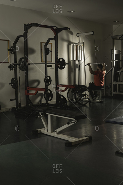 Handicapped man working out lat pulldown training at gym