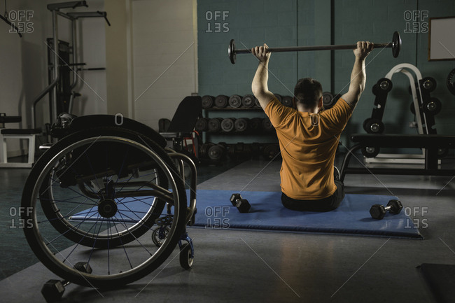 Rear view of handicapped man exercising with barbell in gym