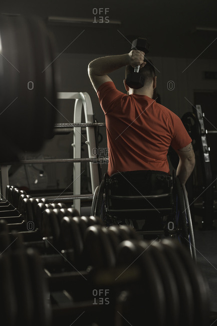 Handicapped man on wheelchair working out with dumbbell in gym