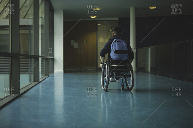 Handicapped man on wheelchair moving in passage at gym