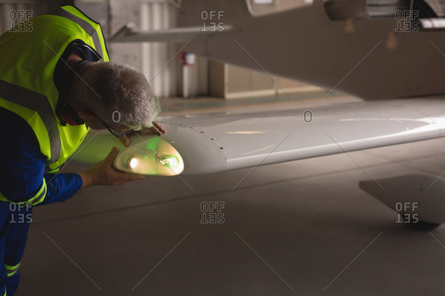 Engineer examining light of aircraft at aerospace hangar