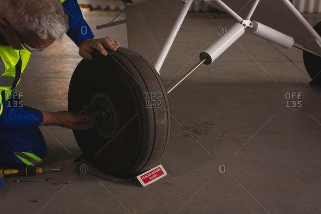 Engineer checking tyre of airplane in aerospace hangar