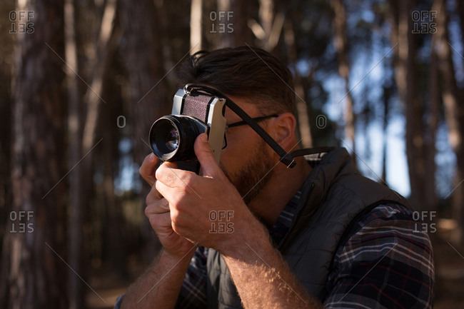 Close-up of man clicking photo with vintage camera in forest