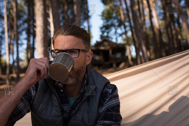 Close-up of man drinking coffee while relaxing on hammock