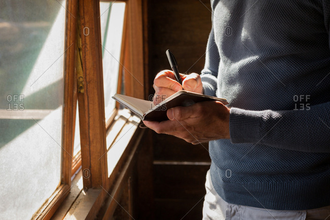 Mid section of man writing note on diary at log cabin