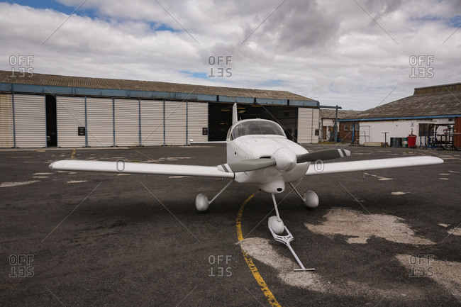 White aircraft parked on airfield