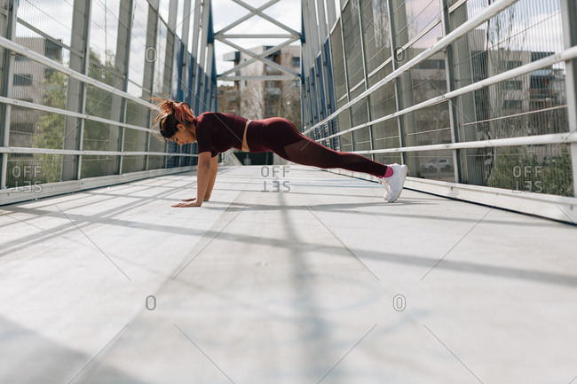 Young hispanic woman doing push ups in urban setting