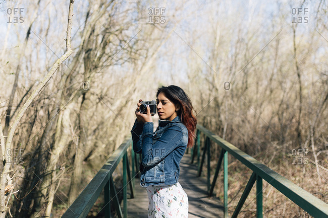 Young woman looking through viewfinder of vintage camera in natural setting