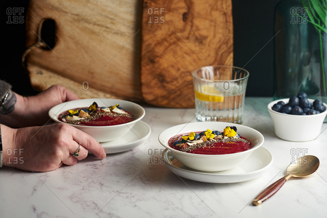 Woman setting breakfast smoothie bowls on a table