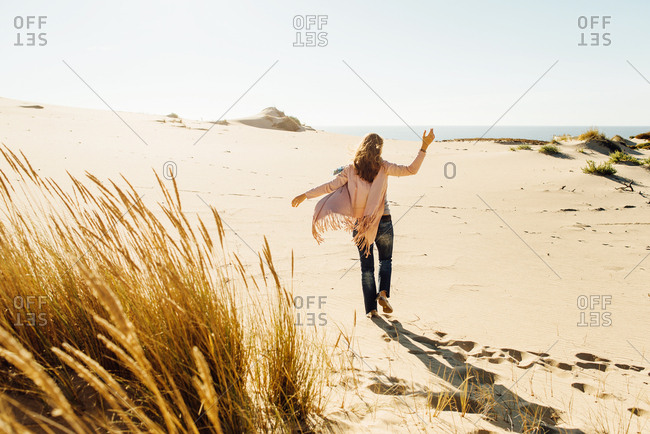 Blonde woman walking towards ocean across sunny beach