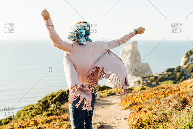 Happy woman skipping along beach path