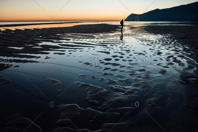 Lone person standing across wet beach viewing ocean sunset