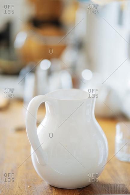 Glossy milk pitcher on wooden kitchen counter