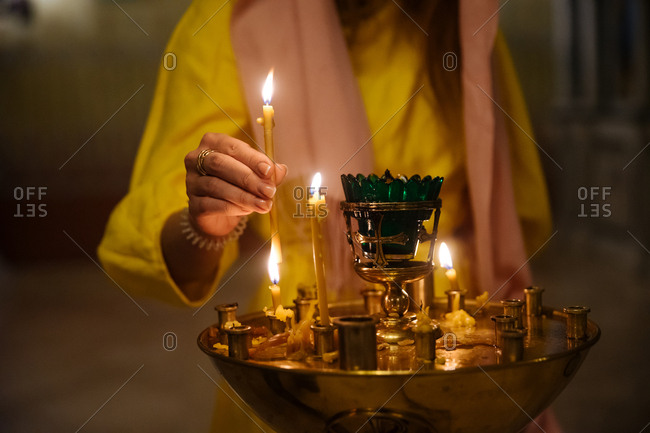 Close up of woman lighting votive candle in church
