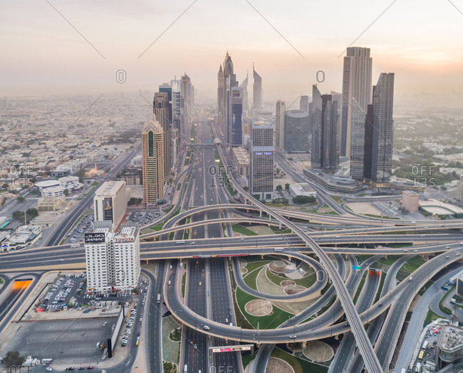 Dubai, United Arab Emirates - July 1, 2017: Aerial view of geometrical traffic lanes and Skyscrapers at sunset