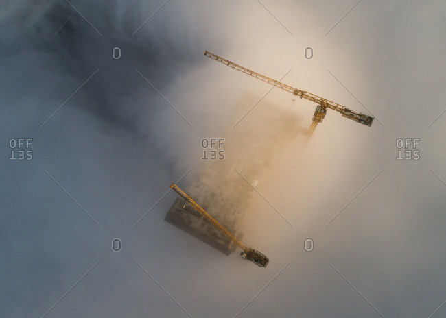 Aerial view of cranes and skyscrapers under construction in the clouds of Dubai, U.A.E.