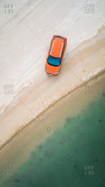 Aerial view of a car parked close by Al Qudra lakes in the middle of Saih Al Salam Desert in Dubai, UAE.