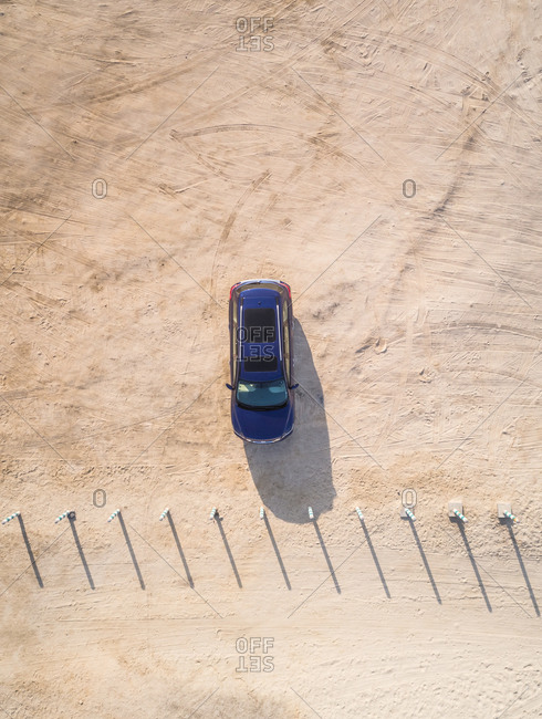 Aerial view of a car parked on the sandy Jabal Ali beach in Dubai, U.A.E.