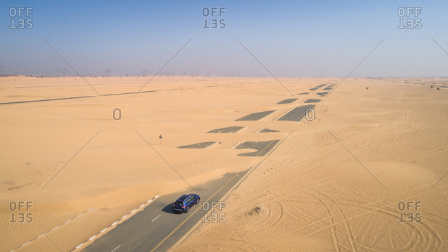 Aerial view of a car driving on a road covered with the sand of Dubai desert, U.A.E.
