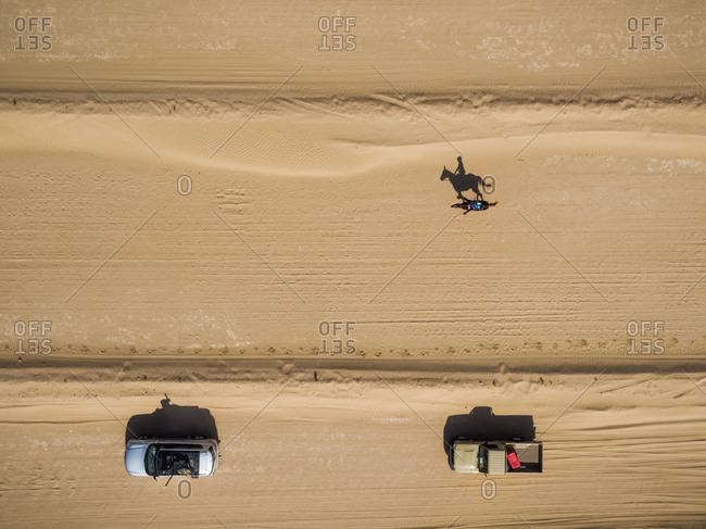 Aerial view of a person on a camel during a race in the desert of Ras Al Khaimah, U.A.E.