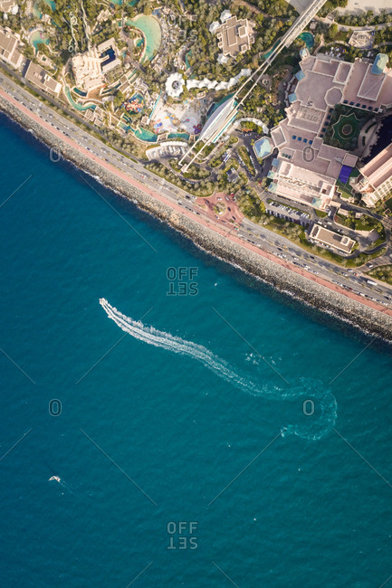 Aerial view of a boat in the sea close to the Palm Jumeirah coast in Dubai, U.A.E.