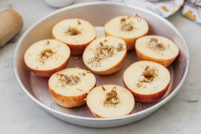 Halved apples topped with nuts in round tin baking pan