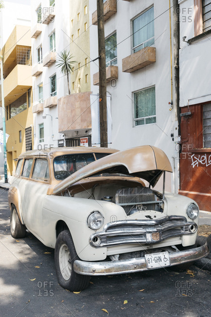Mexico City, Mexico - January 11, 2018: Antique car with open hood parked next to building