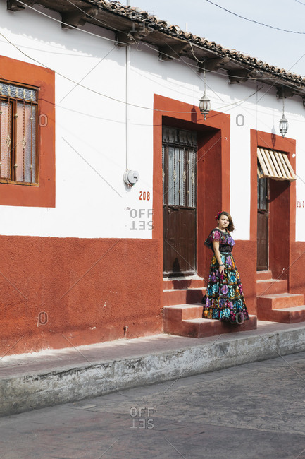 Chiapa de Corzo, Mexico - January 15, 2018: Woman in bold dress standing alone on steps outside